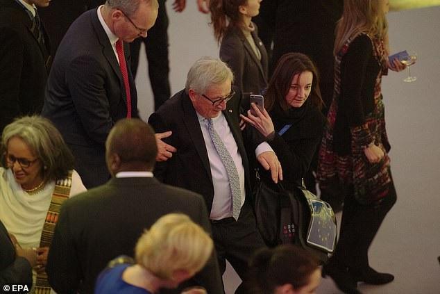 Hình ảnh chụp lại cho thấy ông Juncker đã bước đi lảo đảo, hơi ngả ra đằng sau và cần có 2 trợ lý giúp đỡ để đứng thẳng (Ảnh: EPA)