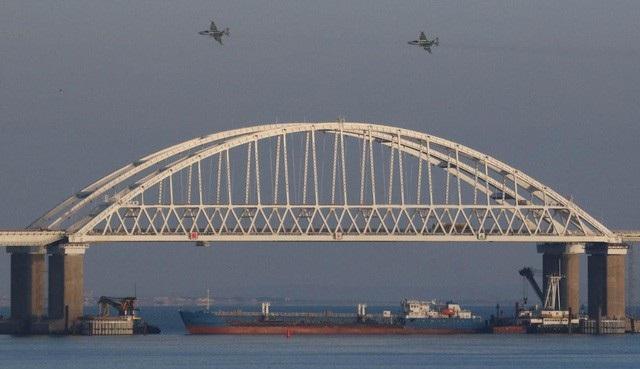 Tàu chở hàng Nga chặn dưới cầu Kerch trong khi máy bay hoạt động trên không trong vụ đụng độ với các tàu chiến Ukraine. (Ảnh: RT)