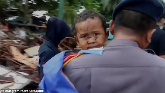 Khoảnh khắc cứu sống bé trai sau 12 giờ mắc kẹt do sóng thần ở Indonesia - Ảnh 2.