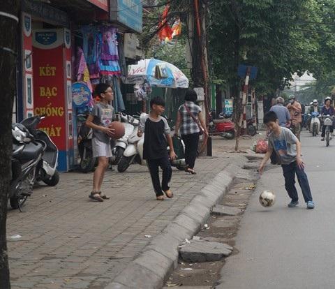 Trẻ em Việt Nam chia nhau từng mét vuông vỉa hè để đá bóng