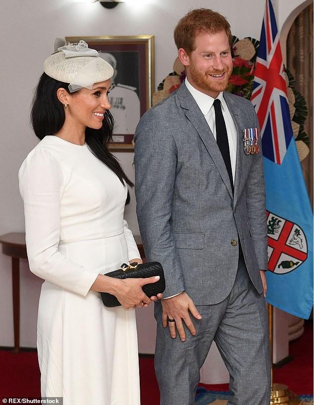 Meghan cầm trên tay chiếc ví Kayu Anna giá 177 bảng Anh.