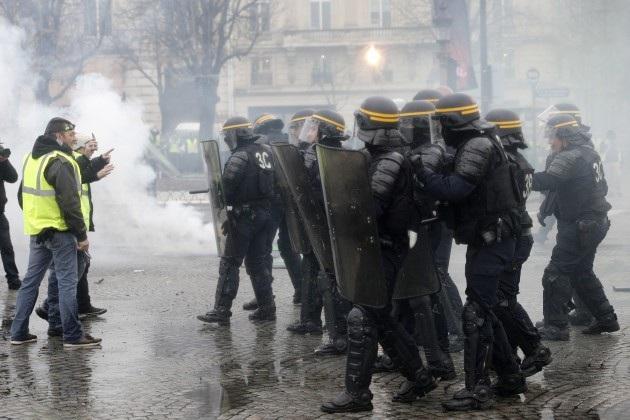Cảnh sát chống bạo động Pháp đối mặt với người biểu tình Áo vàng tại Paris. (Ảnh: AFP)