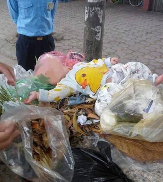 Cháu bé nghi bị bố mẹ bỏ rơi đặt trên thùng rác trên đường Doãn Kế Thiện (Ảnh: Như Cường).