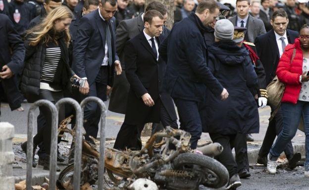 Tổng thống Macron thị sát thiệt hại sau biểu tình tại Paris. (Ảnh: EPA)