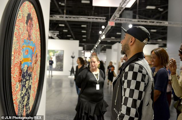 Rapper Swizz Beatz chăm chú ngắm một tác phẩm nghệ thuật.