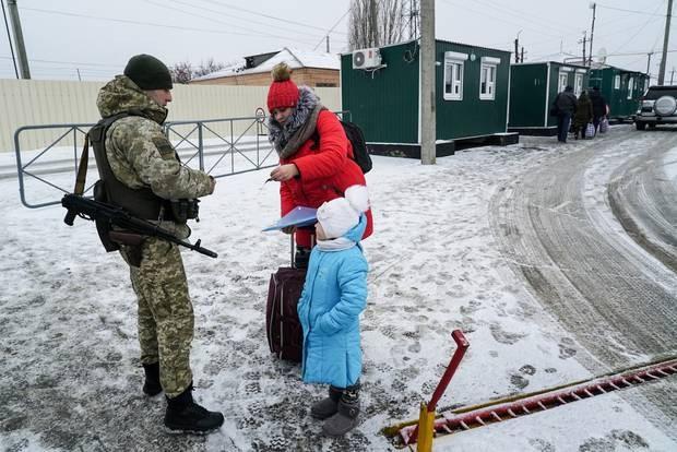 Một phụ nữ trình giấy tờ cho lính biên phòng Ukraine kiểm tra trước khi qua biên giới. Trước đây, người dân hai nước có thể tự do qua lại khu vực này. (Ảnh: AP)
