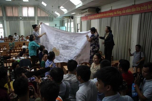 Người dân Thủ Thiêm căng bản đồ để chứng minh phần đất nằm ngoài ranh quy hoạch Khu đô thị mới Thủ Thiêm tại buổi tiếp xúc cử tri của Đại biểu Quốc hội TPHCM (ảnh: Phạm Nguyễn)