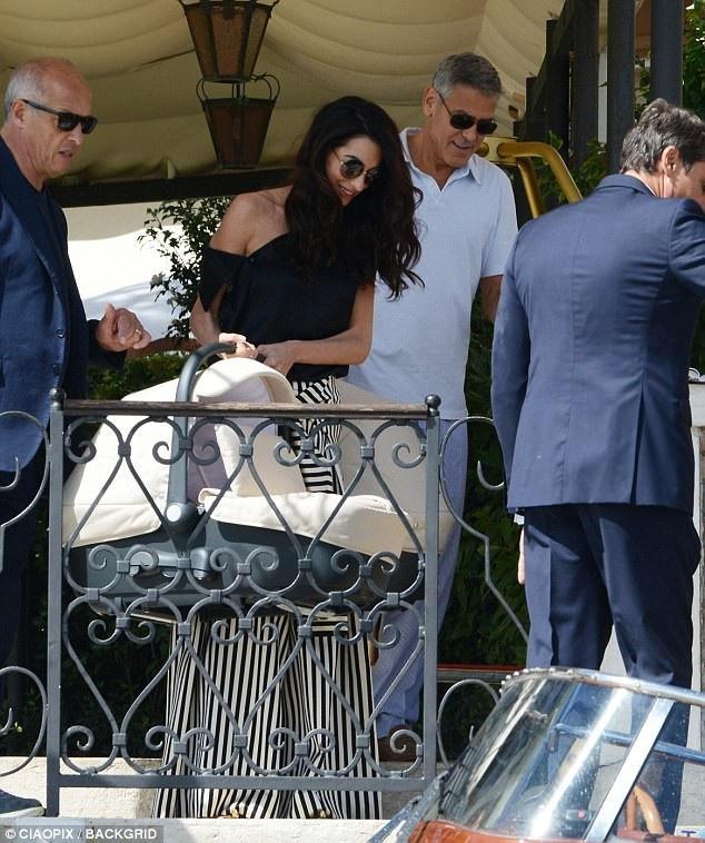 Cặp đôi George và Amal Clooney xách nôi của cặp song sinh 6 tháng tuổi Ella và Alexander.