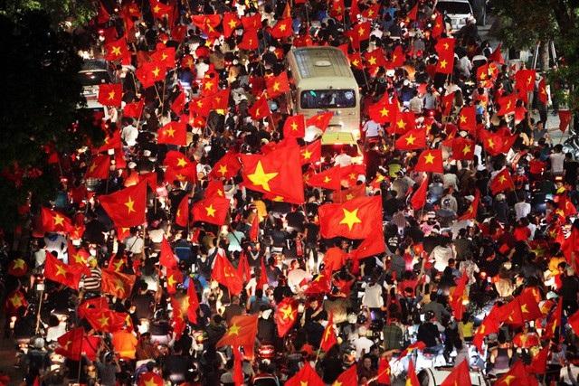 Chiếc xe chờ khách lọt thỏm giữa biến người ăn mừng chiến thắng của đội tuyển U23 Việt Nam (Ảnh: Quý Đoàn)