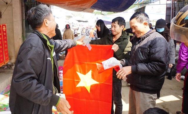 Hai người đàn ông chọn mua cờ Tổ quốc về treo cùng cây nêu trong những ngày Tết