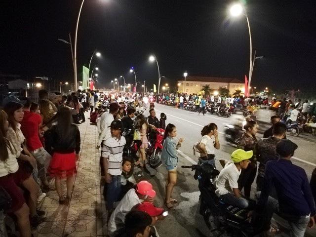 Rất đông người dân tập trung trên cầu vượt qua quốc lộ 1 để chờ xem bắn pháo hoa. (Ảnh: Huỳnh Hải)