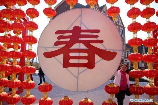 Một phụ nữ đứng bên chữ Mùa Xuân tại thành phố Thập Yển, tỉnh Hồ Bắc, Trung Quốc (Ảnh: News.cn)