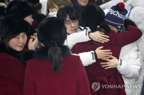 Các vận động viên Triều Tiên (áo đỏ) và các vận động viên Hàn Quốc ôm nhau tại Làng Olympic Gangneung trước khi đoàn Triều Tiên lên đường về nước (Ảnh: Yonhap)