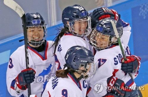 Các vận động viên Triều Tiên và Hàn Quốc ôm nhau ăn mừng trong trận đấu với đội tuyển khúc côn cầu Thụy Điển tại Gangneung trong khuôn khổ Thế vận hội mùa Đông. (Ảnh: Yonhap)