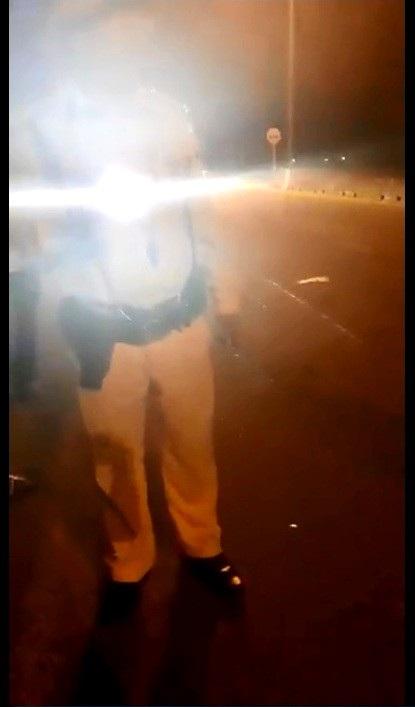 Một cán bộ CSGT có hành động rọi đèn pin vào mặt người dân