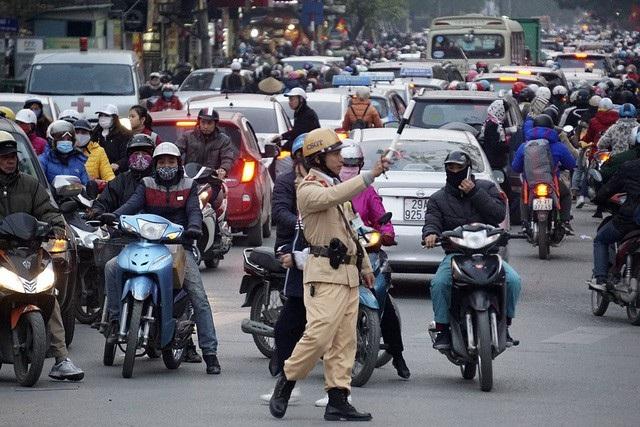 Cảnh sát giao thông điều phối phương tiện đông đúc trên phố Tôn Thất Tùng lúc 18h10.