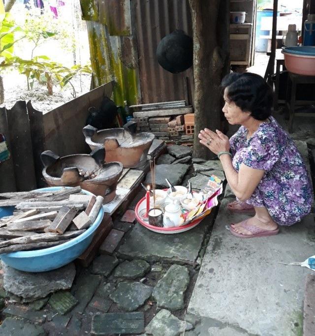 Một người dân cúng ông Táo ngay tại lò củi làm bằng đất nung truyền thống...