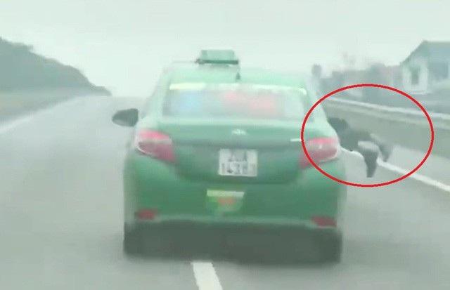 Hình ảnh chiến sĩ công an bị tài xế taxi hất lên nắp capo. (Ảnh cắt từ clip)
