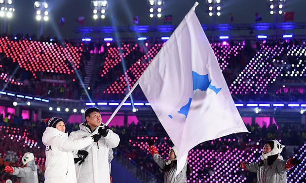 Các CĐV Hàn Quốc và CHDCND Triều Tiên diễu hành dưới lá cờ in hình bán đảo Triều Tiên