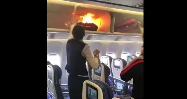 Tiếp viên hàng không đang cố gắng dập tắt ngọn lửa bốc ra từ bên trong khoang hành lý xách tay