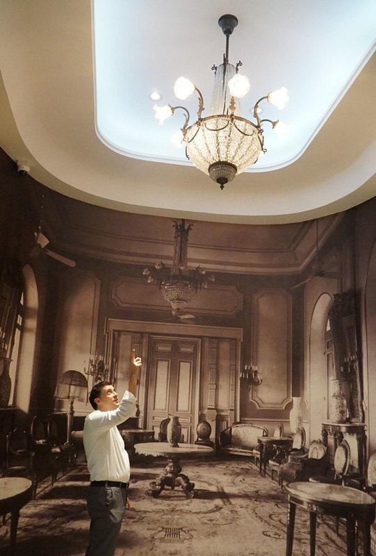 Một bức ảnh lớn về căn phòng trong dinh Thống đốc được phóng lớn trên tường, tạo cảm giác cho người xem như được đứng trong không gian hơn một thế kỷ trước. GS Adward đang chỉ chiếc đèn thật bên ngoài được lãnh đạo Hội trường Thống Nhất đặt làm giống với chiếc trong tấm ảnh.