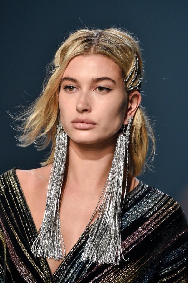 """Người mẫu Mỹ Hailey Baldwin với đôi khuyên tai ánh bạc """"cự phách"""" bổ trợ cho bộ trang phục lấp lánh các dải màu kim tuyến, tại một show trình diễn thuộc Tuần lễ Thời trang New York."""
