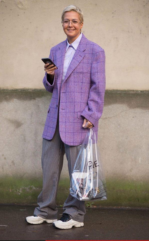 """Một tín đồ yêu thời trang đến dự một sự kiện tại Tuần lễ Thời trang Paris với một """"cây đồ"""" đậm chất hoài cổ, gồm mốt kẻ ca-rô, sơ-mi cổ điển, giày thể thao to bự - thiết kế phổ biến của những thập niên trước giờ đang gây sốt trở lại, và một chiếc túi nhựa trong suốt có giá 600 USD."""