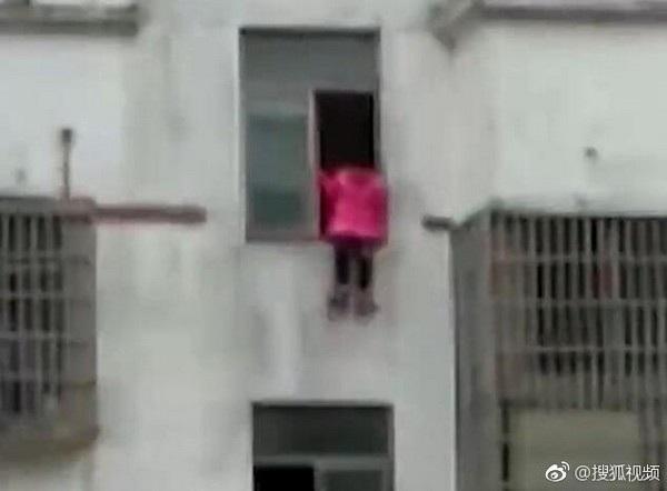 Hình ảnh cô bé ngồi vắt vẻo trên cửa sổ tầng 15 khiến nhiều người hoảng sợ