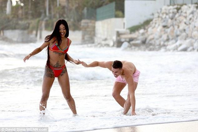 Cặp đôi trẻ hạnh phúc nô đùa trên bãi biển