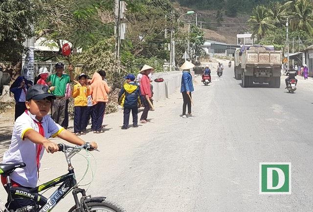 Bác bảo vệ Nguyễn Văn Châu (56 tuổi, bảo vệ Trường tiểu học Phước Đồng (TP Nha Trang, tỉnh Khánh Hòa) giơ tấm biển Stop ra hiệu cho các xe tải đi chậm để dắt học sinh qua đường. Đều đặn mỗi ngày ông Châu dắt học sinh qua đường 4 lần vào trước và sau mỗi buổi học.