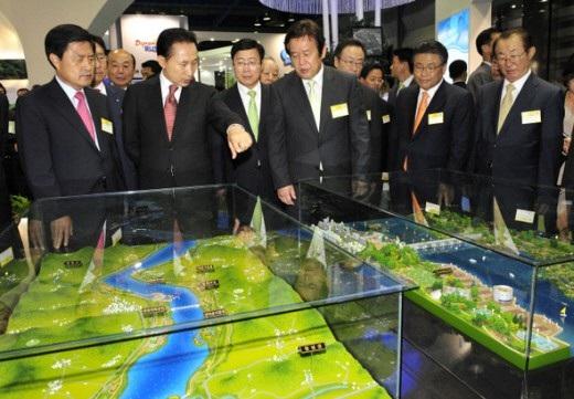 Ông Lee Myung-bak (thứ hai từ trái qua) quan sát mô hình dự án Hồi phục Bốn dòng sông tại trung tâm triển lãm ở Seoul (Ảnh: Hani)