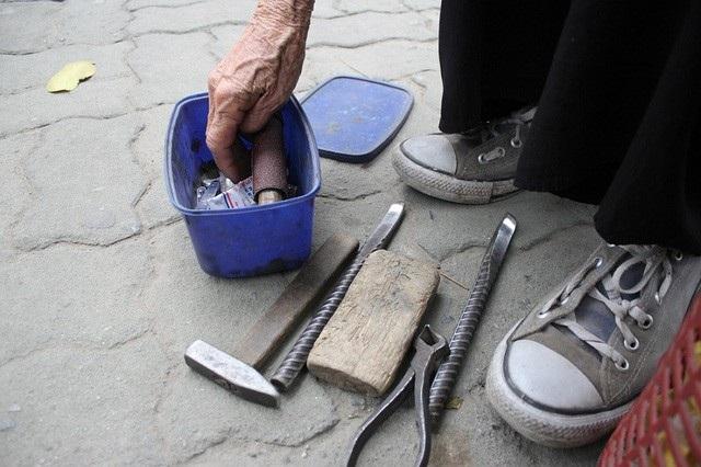 Đồ nghề của cụ Vân đơn giản là một chiếc bơm cũ kỹ, dăm miếng vá xe và búa, kìm. (Ảnh: Hà Trang)