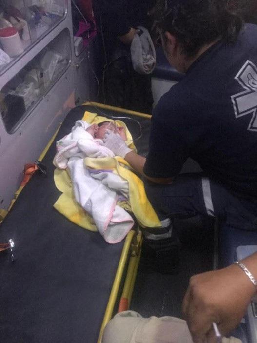 Cậu bé được quấn chăn và cho thở bình oxy