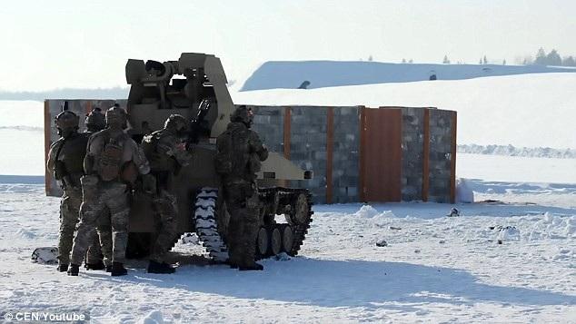 Xe tăng không người lái của Nga đã phô diễn khả năng phóng hỏa lực xuyên qua những bức tường tại một thao trường ở vùng Moscow. Một nhóm binh sĩ Nga cũng tham gia hỗ trợ hoạt động của xe tăng. (Ảnh: CEN)