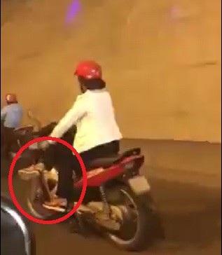 Người phụ nữ có hành động gác chân sang một bên khi đang điều khiển xe máy như diễn xiếc trên đường (Ảnh: Cắt từ clip).