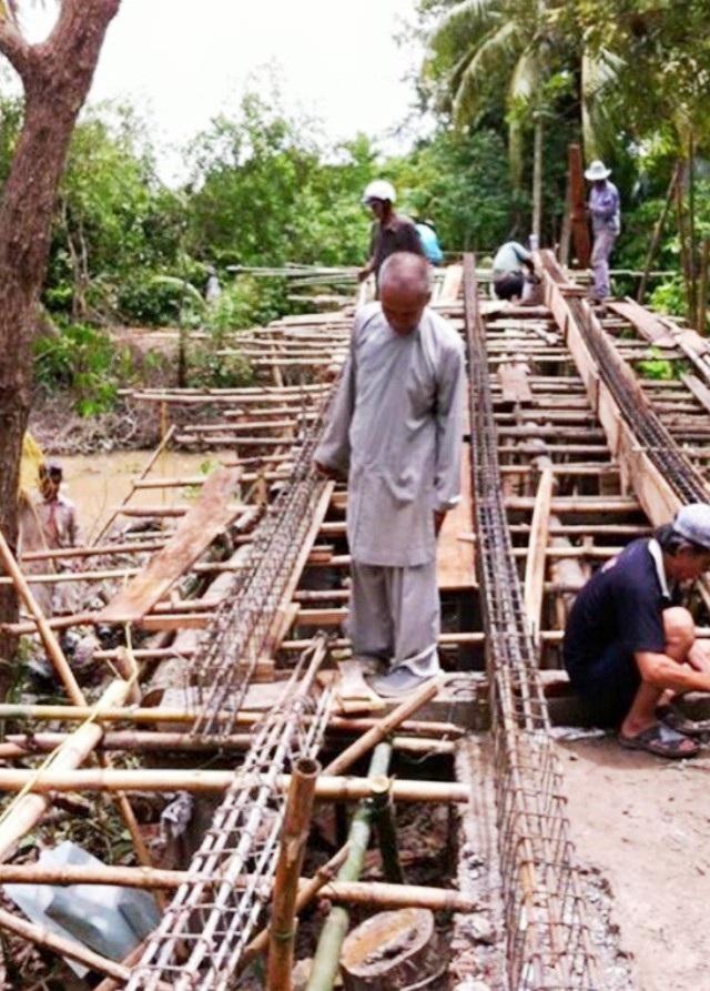 Thượng tọa Thích Minh Hạnh tại một cây cầu đang xây dựng.