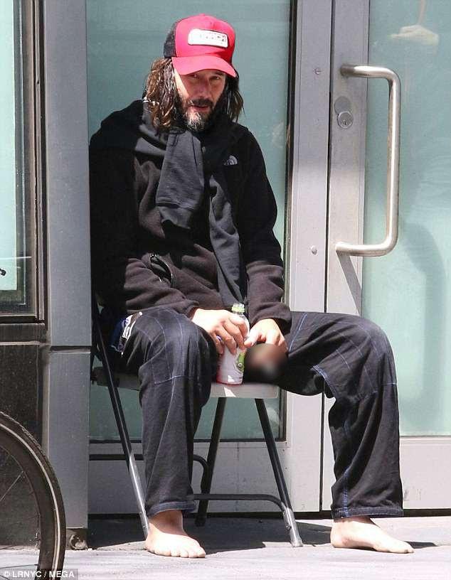 Sẽ không ai nhận ra nổi Keanu Reeves trong diện mạo này. Anh ngồi bên ngoài một studio trong bộ dạng như người lang thang.