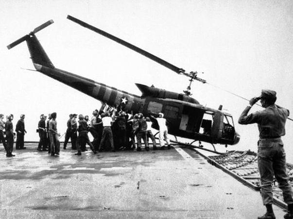 Các quân nhân Mỹ trên tàu USS Blue Ridge ra sức đẩy một trực thăng trên tàu xuống biển để lấy chỗ cho các chuyến bay sơ tán khác đáp xuống.