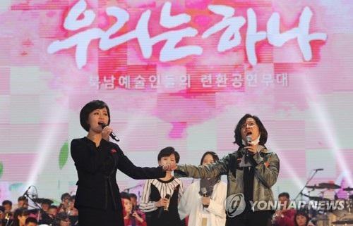 """Bầu không khí bắt đầu nóng lên với những màn vỗ tay không ngớt của khán giả khi ca sĩ Lee Sun-hee (phải) của Hàn Quốc nắm tay ca sĩ Kim Ok-ju của Triều Tiên thể hiện chung một bài hát. Khán giả bắt đầu reo hò khi hai nữ ca sĩ biểu diễn ca khúc mang tên """"Paektu và Halla là tổ quốc của chúng ta"""" với sự hỗ trợ của dàn nhạc Samjiyon. (Ảnh: Yonhap)"""