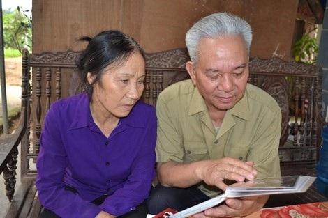 Ông Toàn và vợ xem lại những bức ảnh cưới.
