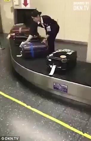 Nữ nhân viên người Nhật cẩn thận lau từng chiếc vali cho khách trên băng chuyền