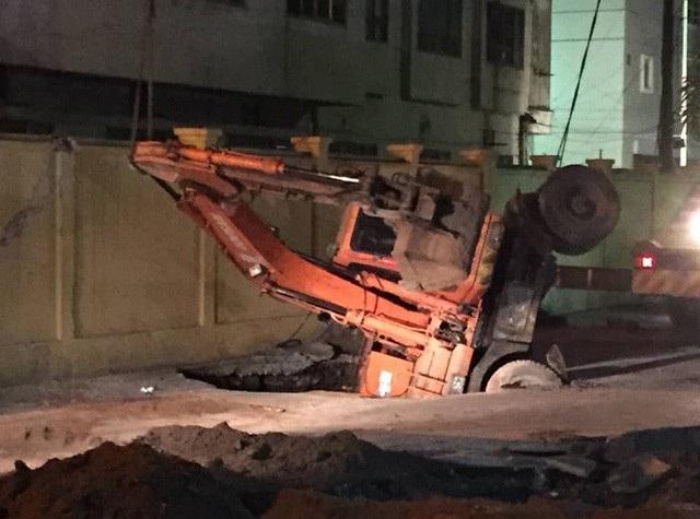 """Người cùng xe máy tại một khu dân cư bất ngờ bị một hố tử thần rộng hàng chục mét vuông """"nuốt"""" gọn. Thậm chí máy xúc đến khắc phục hậu quả cũng bị hố sâu cuốn xuống luôn."""