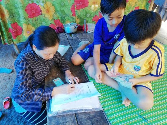 Chị Lê Kim Hằng ký nhận tiền hỗ trợ của bạn đọc báo Dân trí.