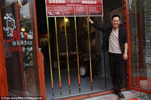 Ông Zhao chủ quán bên khung cửa kim loại của nhà hàng