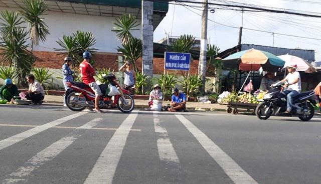 Dù có bảng cấm nhưng tình trạng chợ mua bán vẫn mọc lên ở một số tuyến đường trên địa bàn TP Cà Mau, vi phạm hàng lang an toàn đường bộ. (Ảnh: CTV).