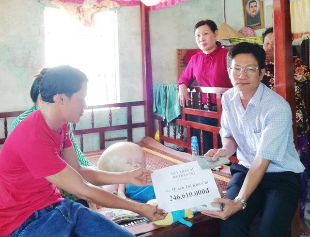 PV Dân trí đang trao tiền bạn đọc hỗ trợ cho gia đình chị Quách Thị Kim Chi.
