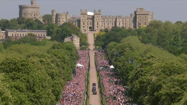 Người dân và du khách vây kín hau bên đường reo hò khi đoàn xe chở cô dâu tiến về lâu đài Windsor.