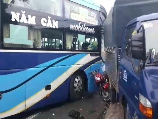 Xe máy bị kẹp giữa xe khách và xe tải, nạn nhân đi xe máy thoát chết trong gang tấc.