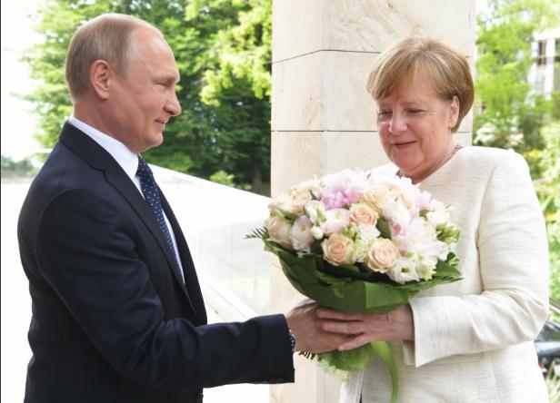 Tổng thống Putin tặng hoa cho Thủ tướng Merkel hôm 18/5 (Ảnh: RT)
