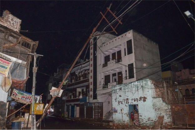 Cơn bão làm bật gốc hàng trăm cột điện - Ảnh từ AFP.